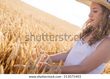 Beautiful young girl with her hat on, standing in wheat field at sunset. Selective focus. Toned in warm colors. - stock photo