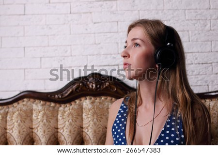 Beautiful young girl with long blond hair with headphones sitting on couch classic - stock photo