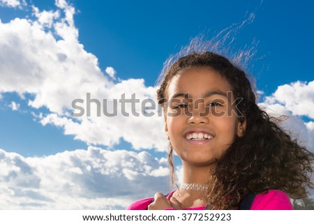 Beautiful young girl with long curly hair wearing a red t-shirt.  Portrait of happy Brazilian child against blue sky with white clouds background, pefect for family blogs and magazines - stock photo
