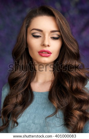 Beautiful young girl with long wavy brunette hair and bright evening make-up looking down posing against purple flowers background. Shallow DOF - stock photo