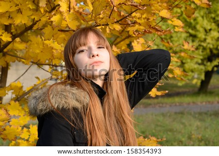Beautiful young girl with red hair, against the backdrop of golden autumn - stock photo
