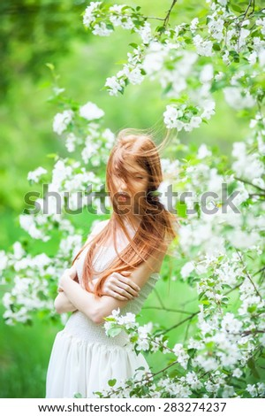 Beautiful young girl with red hair near apple tree - stock photo