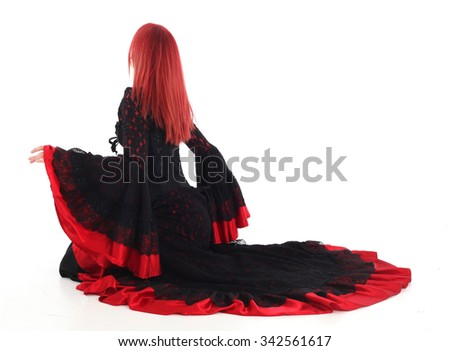 Beautiful young girl with red hair, wearing a long  gothic black and red flamenco lace gown with black corset. kneeling on the ground. isolated on white background. - stock photo