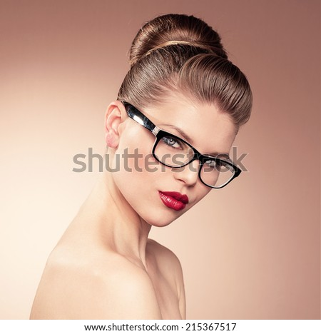 Beautiful young girl with retro hairdo in spectacles posing in studio. Portrait of lovely blue eyed woman wearing eyeglasses.   - stock photo
