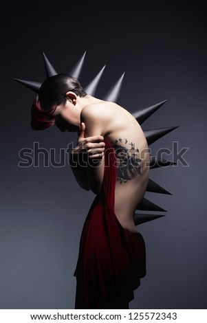 beautiful young girl with thorns on her back and head posing in front of dark background - stock photo