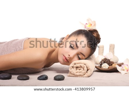 Beautiful young girl with towel lying on massage table, isolated on white - stock photo