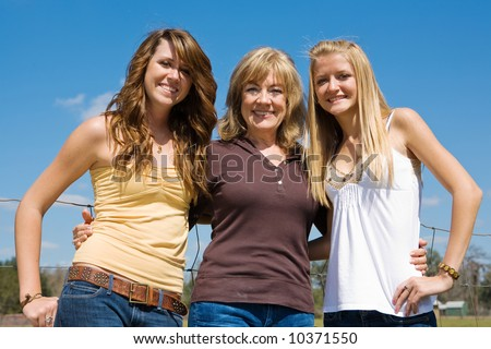 Beautiful young grandmother and granddaughters outdoors on their farm. - stock photo