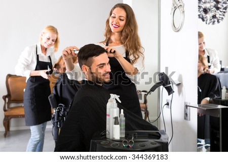 Beautiful young hairdresser working in a salon is making a haircut for a handsome man - stock photo