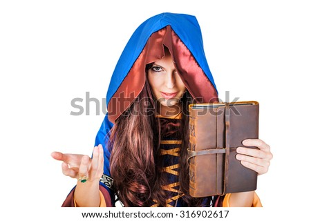 Beautiful young halloween witch wearing vintage gothic dress with hood holding magical book of spells in old leather cover isolated on white background - stock photo