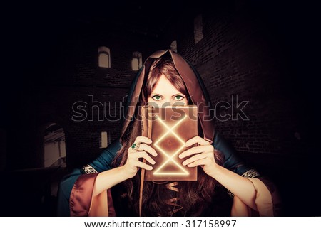 Beautiful young halloween witch wearing vintage gothic dress with hood holding magical book of spells in old leather cover inside ancient dark castle - stock photo