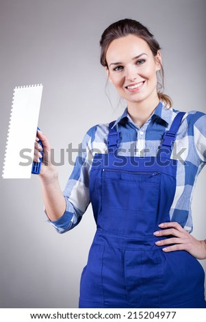 Beautiful young handywoman standing with trowel and smiling - stock photo