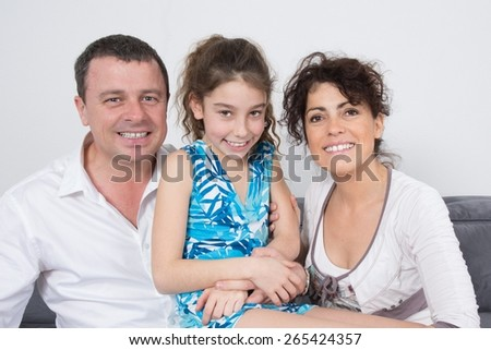 Beautiful young happy family with daughter sitting on the sofa - indoors - stock photo