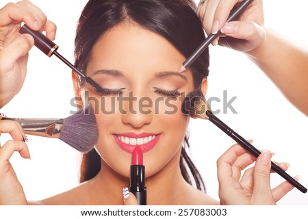 Beautiful young happy fashion model at beauty treatment applying professional makeup. Isolated on white background - stock photo
