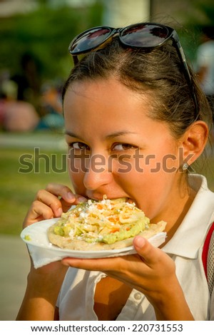 beautiful young happy girl eating a tostada soft taco in guatemala - stock photo