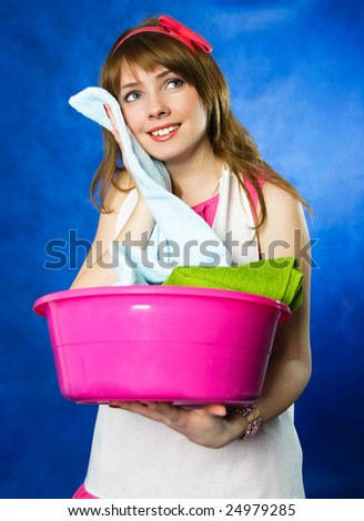 beautiful young happy housewife surprised with the softness ot the towels she has just washed - stock photo