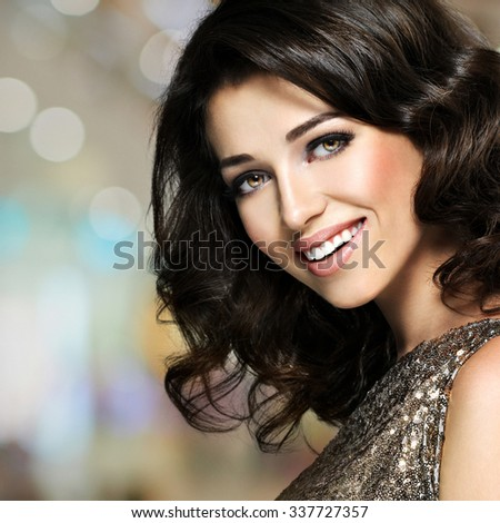 Beautiful young happy laughing woman with brown curly hairs. Pretty fashion model with dark eye makeup - stock photo