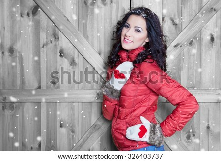 Beautiful  young happy smiling woman wearing winter  jacket and gloves covered with snow flakes. Christmas portrait concept.  - stock photo