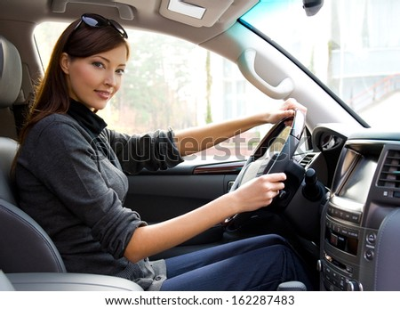 beautiful young happy woman posing inside of  the new car  - stock photo