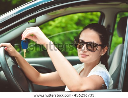 Beautiful young happy woman with car key. Toned image - stock photo