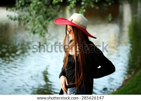 Beautiful young hippie girl outdoors enjoying nature. Trendy boho fashion Caucasian woman wearing black cardigan, hat and denim shorts. - stock photo