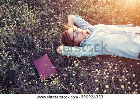 Beautiful young hipster laying down on the meadows field smiley  - stock photo