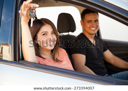Beautiful young Hispanic woman sitting in a car with her husband and showing their car keys - stock photo