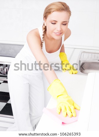 beautiful  young housewife wearing gloves cleaning the furniture  in the kitchen at home - stock photo
