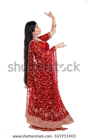 Beautiful young indian bride in traditional clothing with bridal makeup and jewelry. gorgeous brunette bride traditionally dressed. Woman bollywood dancer in Sari. Arabian bellydancer  - stock photo
