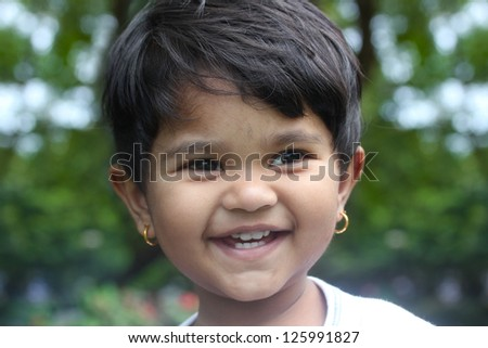 Beautiful young indian girl child smiling & happy and having fun at a outdoor park. The kid is 2 years old - stock photo