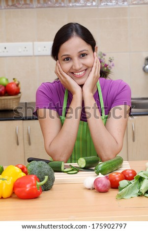 Beautiful young Indian woman in kitchen - stock photo
