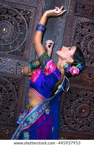 Beautiful young indian woman in traditional clothing near the carving wooden door - stock photo