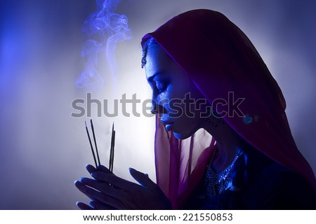 Beautiful young indian woman in traditional clothing with incense and oriental jewelry. Beautiful Girl praying (blue lens effect) - stock photo