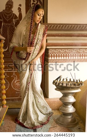 Beautiful young indian woman in traditional clothing with incense, bridal makeup and oriental jewelry. Girl bollywood dancer in Sari, eastern palace. Beautiful princess praying. Eastern fairy tale - stock photo