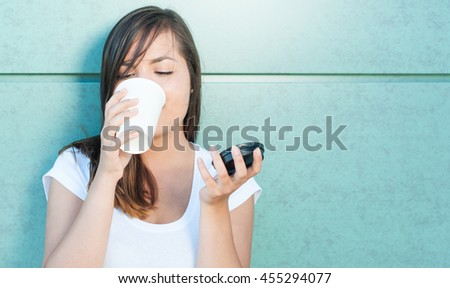 Beautiful young lady holding coffee mug and drinking outside on green wall with copy text area - stock photo