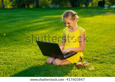Beautiful young lady is chatting with friends outdoors as it is very useful to be in nature. Laptop is the best friend for a child nowadays. Green and vast meadow. - stock photo