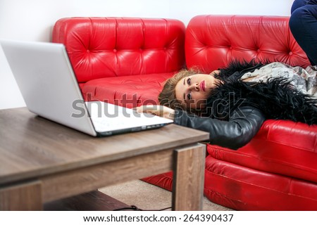 Beautiful young lady laying on sofa and using laptop. - stock photo