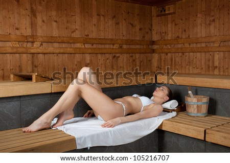 Beautiful young lady lying on a wooden bench in a sauna - stock photo