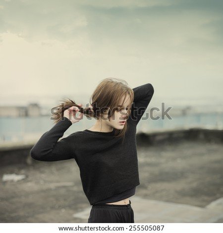 beautiful young lady on the roof in the spring - stock photo