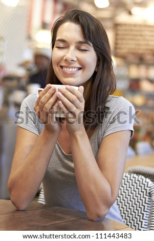 Beautiful young lady smiling while enjoying her warm coffee in a coffee shop - stock photo