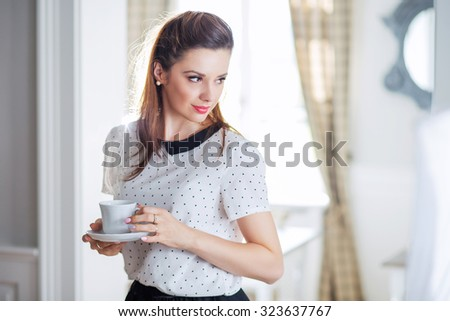 Beautiful young lady with coffee cup - stock photo