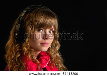 Beautiful young lady with headphones looking at camera - stock photo