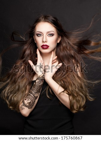 Beautiful young lady with painted hands mehendi and with flying hair. Beauty photo - stock photo