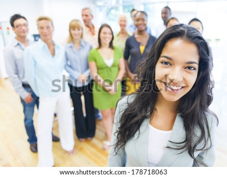 Beautiful Young Latin Woman Standing In Front of Crowd at Office - stock photo