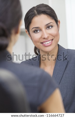 Beautiful young Latina Hispanic woman or businesswoman in smart business suit sitting at a desk in an office having a meeting with colleague - stock photo