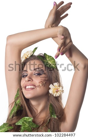 Beautiful young laughting woman with flowers, leaves in her hair and original make up over white - stock photo