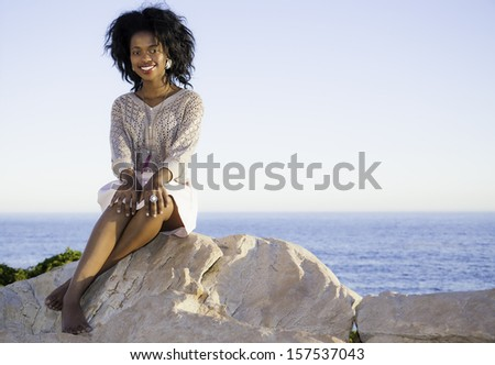 beautiful young long hair woman sitting on the rocks and posing at sunset - stock photo