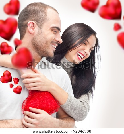 Beautiful young love couple embracing against a white background and many red hearts flying around them - stock photo