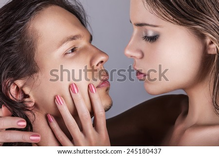 Beautiful young lovers in love embracing. Sexy beauty couple on a grey background - stock photo