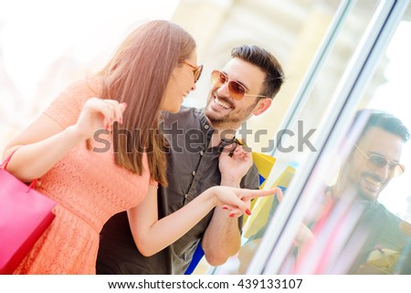 Beautiful young loving couple carrying shopping bags on shoulders and enjoying together.They are having a great time. - stock photo