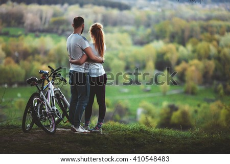 Beautiful young loving couple hugging at sunset, there are two bikes. The concept of happiness, peace and love - stock photo